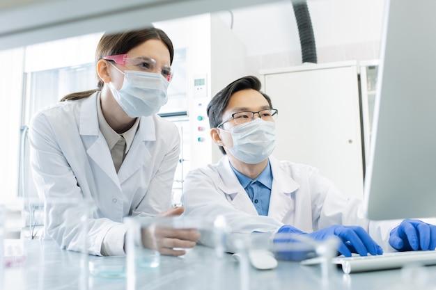 Due giovani lavoratori di laboratorio interculturale in maschere, occhiali da vista, guanti e camici bianchi guardando lo schermo del computer durante la ricerca scientifica