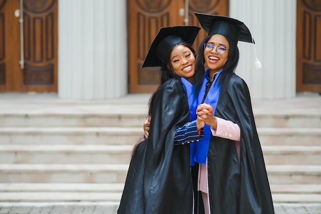 Due giovani donne in costumi di laurea in posa davanti alla telecamera al campus universitario, in possesso di diplomi, risate e abbracci, felice giorno della laurea, ritratto del primo piano