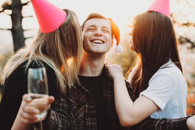 Due giovani donne in cappelli da festa sorridendo e baciando ragazzo allegro con bicchiere di vino nelle guance mentre celebravano il natale nella natura