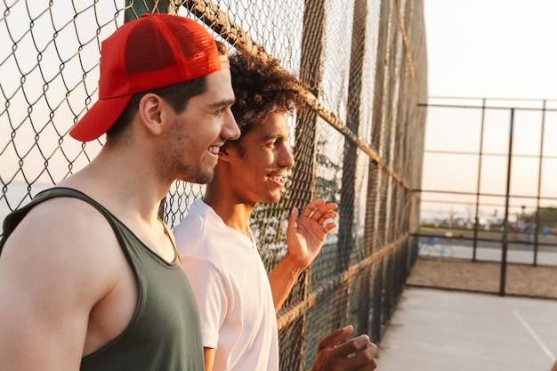 Due giovani ridendo giocatori multietnici di pallacanestro degli uomini