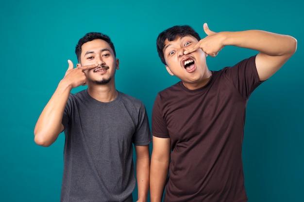 Due giovani che ridono e fanno il tifo con il suo amico su sfondo blu
