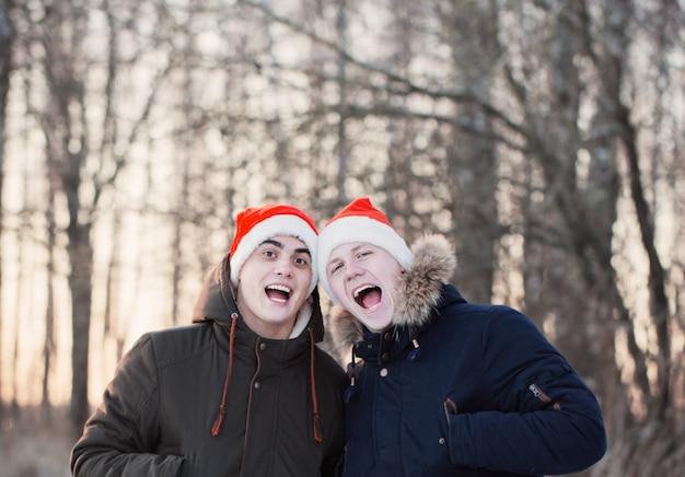 Due giovani uomini in cappelli di natale babbo natale