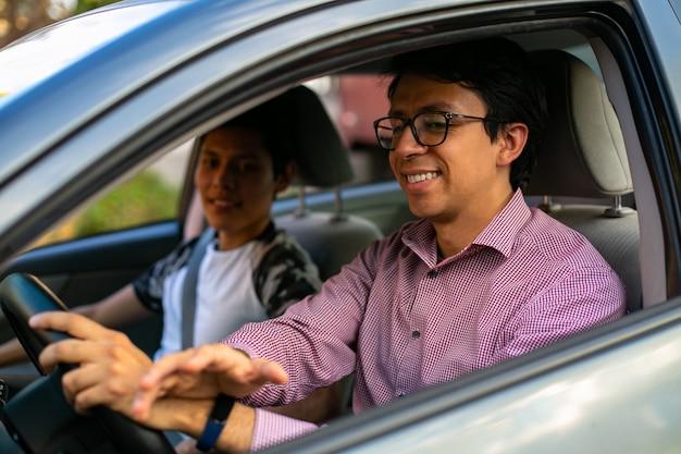 Due giovani in una sessione di guida e l'istruttore sta insegnando al giovane a guidare