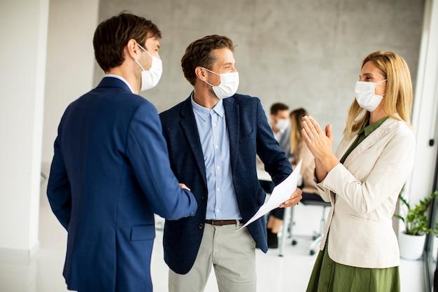 Due giovani uomini e donne che discutono con la carta in mano al chiuso in ufficio con i giovani lavora dietro di loro