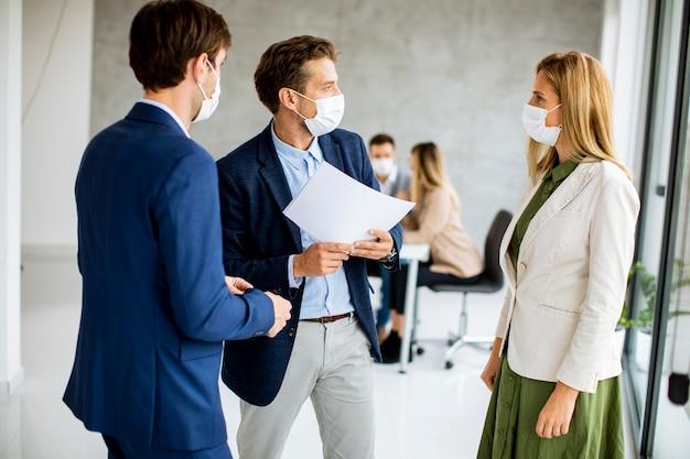 Due giovani uomini e donne che discutono con la carta in mano all'interno dell'ufficio con i giovani che lavorano dietro di loro