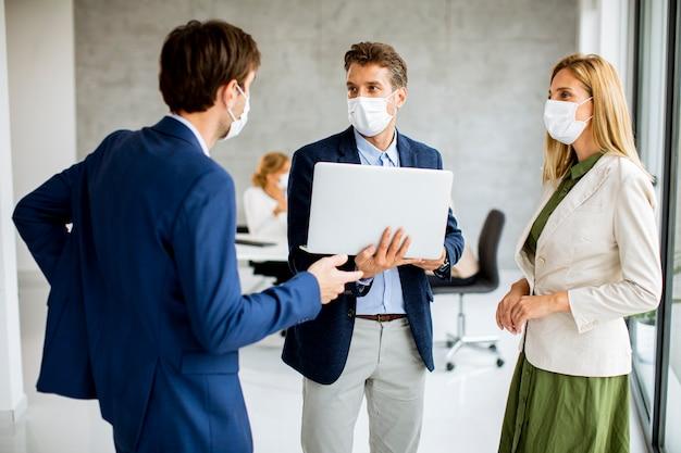 Due giovani uomini e una donna in piedi con il portatile in mano al chiuso in ufficio con i giovani lavora dietro di loro