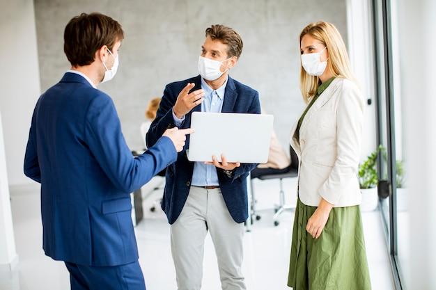 Due giovani uomini e una donna in piedi con il computer portatile in mano all'interno dell'ufficio con i giovani che lavorano dietro di loro