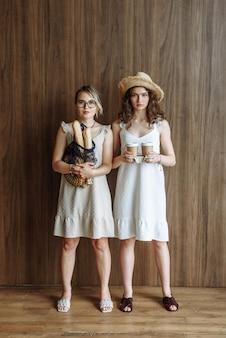 Due giovani donne modello che posano in piedi in studio in abiti che tengono una borsa di corda con pane e tazze con caffè