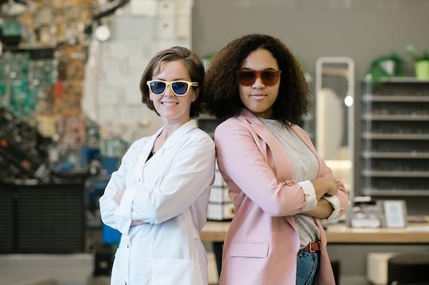 Due giovani femmine multiculturali in occhiali da sole in piedi vicini tra loro all'interno del negozio di ottica