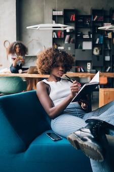 Due giovani donne multirazziali che scrivono e lavorano nel moderno spazio di coworking