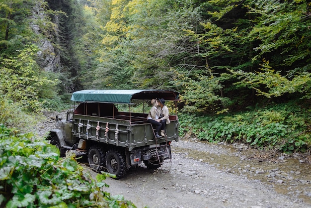 Due giovani si baciano in una grossa macchina. persone in abiti da campeggio in mezzo alla foresta e alle montagne.