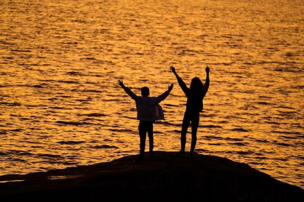 Due giovani in piedi sulla roccia davanti all'acqua con le mani in alto guardando il tramonto