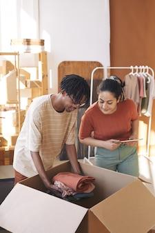 Due giovani che lavorano in team stanno mettendo i vestiti nuovi nella scatola di cartone e preparano il pacco per la consegna in magazzino