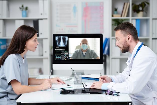 Due giovani professionisti che si consultano con un collega durante la comunicazione online mentre sono seduti davanti al monitor del computer in uno studio medico