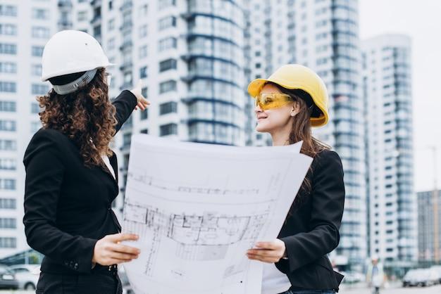 Due giovani graziosi imprenditori industriali ingegneri industriali in caschi da costruzione su uno sfondo di costruzione di vetro. piano di costruzione, architetto, progettista, riuscito