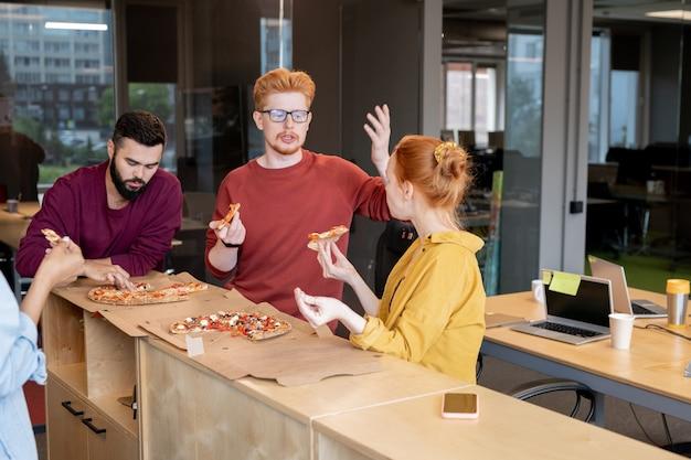 Due giovani colleghi dai capelli rossi in abbigliamento casual gesticolano durante un caldo dibattito in pausa pranzo mentre mangiano pizza da tavola in ufficio