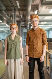 Due giovani colleghi dai capelli rossi in abbigliamento casual intelligente in piedi uno accanto all'altro davanti alla telecamera contro l'interno dell'ufficio openspace