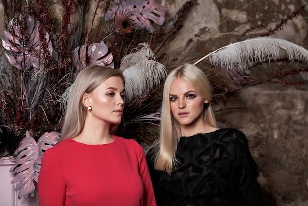 Due giovani ragazze sexy con lunghi capelli biondi alla moda e trucco alla moda glamour e abiti rossi vicino al pianoforte