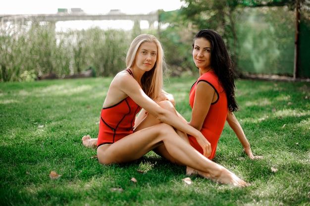 Due giovani donne sexy vestite in costume da bagno seduto sull'erba verde