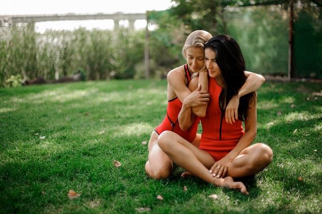 Due giovani donne sexy in costumi da bagno che abbracciano e che si siedono sull'erba verde Foto Premium