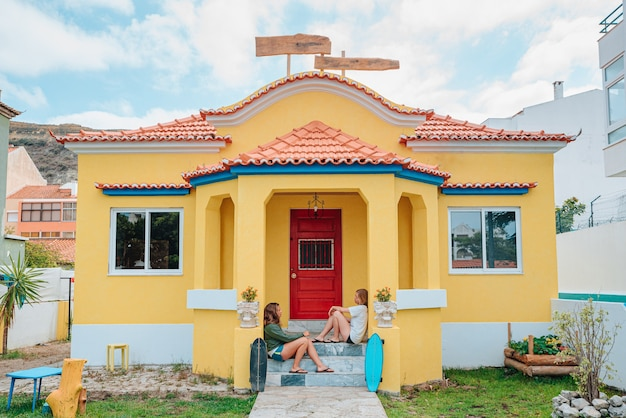 Due giovani womans skater seduti sotto il portico della loro casa estiva