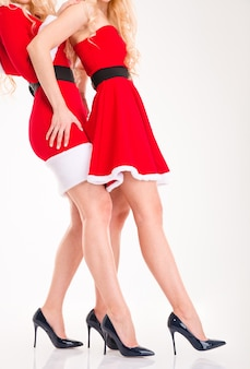 Due giovani donne magre in abiti rossi di babbo natale con gambe attraenti in scarpe nere col tacco alto