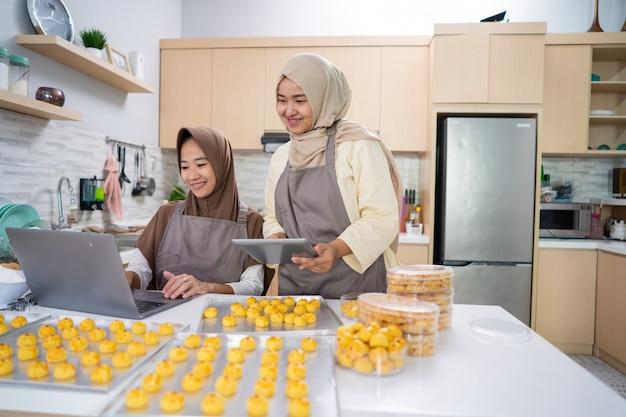 Due giovani piccoli imprenditori musulmani che vendono torta nastar fatta in casa da casa. donna musulmana che cuoce insieme la torta dell'ananas