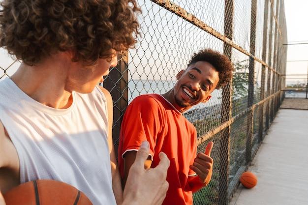 Due giovani giocatori di pallacanestro multietnici sorridenti degli uomini