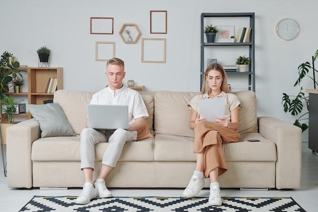 Due giovani studenti seduti sul divano in soggiorno mentre una ragazza guarda le informazioni sui documenti e un ragazzo che legge dati online