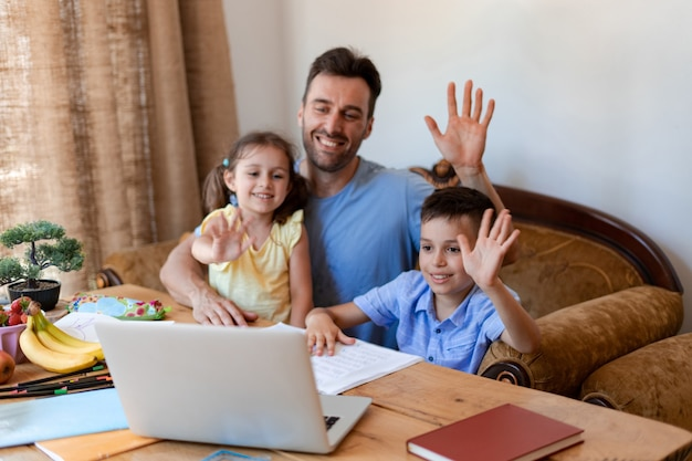 Due giovani studenti e il loro padre salutano un insegnante che ha appena tenuto una lezione online per i bambini che studiano a casa durante la quarantena.