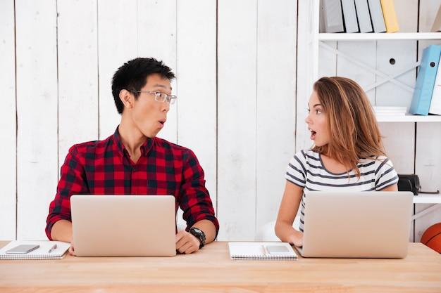Due giovani studenti che sono rimasti scioccati da ciò che è stato visto nei laptop in classe. guardandosi l'un l'altro