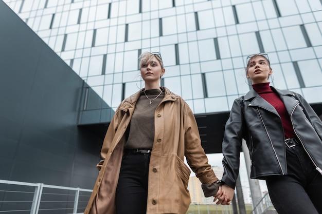 Due giovani donne alla moda con una giacca di pelle alla moda e jeans neri si tengono per mano e camminano vicino a un edificio moderno intorno alla città