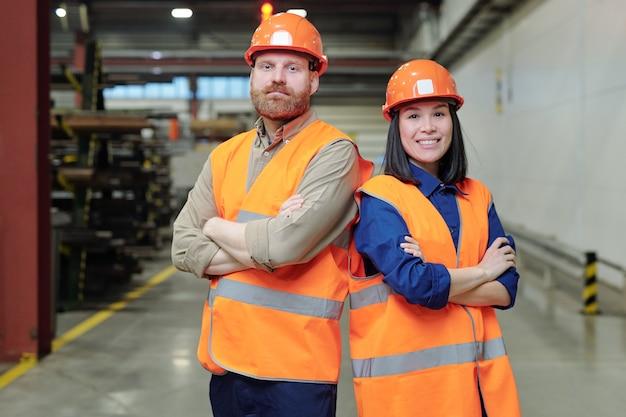 Due giovani ingegneri di successo in elmetto protettivo e abbigliamento da lavoro che incrociano le braccia per il petto mentre si trovano in fabbrica