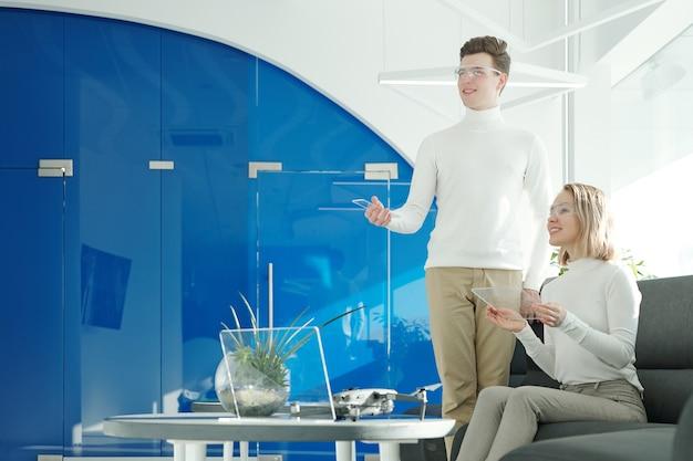 Due giovani sviluppatori di software di successo con occhiali intelligenti che scansionano le informazioni attraverso gadget trasparenti e guardano il display