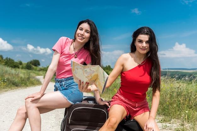 Due giovani donne turistiche che fanno l'autostop sulla strada e si prendono una pausa godendosi una bella giornata di sole estivo