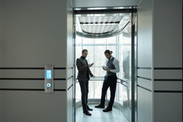 Due giovani imprenditori maschi ben vestiti che utilizzano gadget mobili in ascensore del moderno centro business
