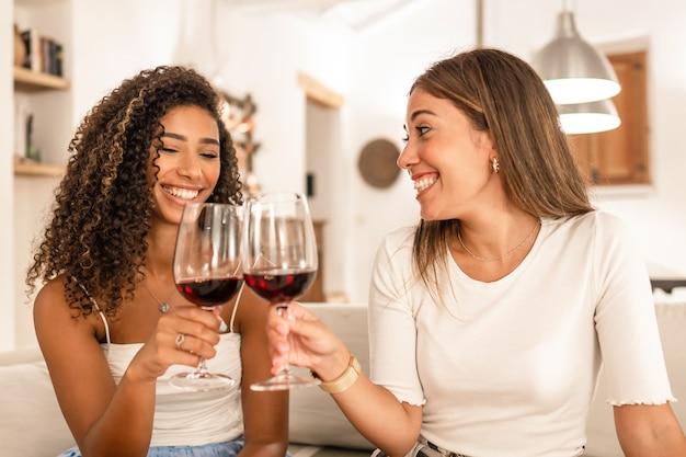 Due giovane donna che celebra a casa, brindando con bicchieri di vino rosso