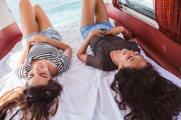 Due giovani donne sdraiate vicino gli occhi rilassano all'interno del furgone retrò