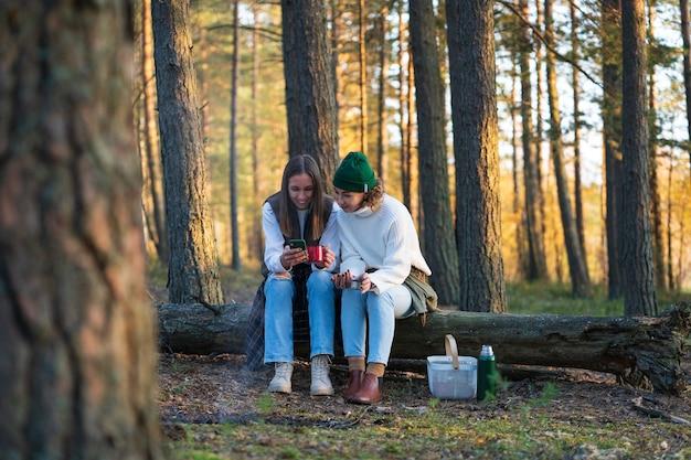 Due giovani donne si rilassano dopo aver raccolto le bacche si siedono sull'albero nella foresta bevono il tè con lo smartphone in mano