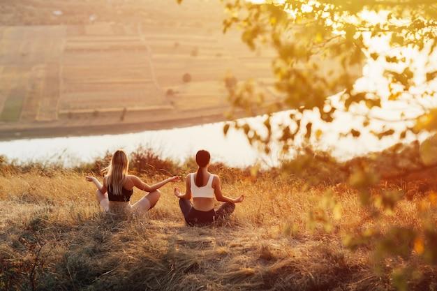 Due giovani donne praticano yoga sulla montagna con il fiume. stanno meditando sulla cima di una collina al tramonto.
