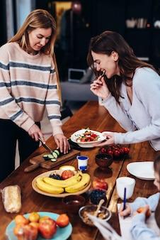 Due giovani donne stanno preparando il pranzo, una sta tagliando le verdure per l'insalata, l'altra sta assaggiando.