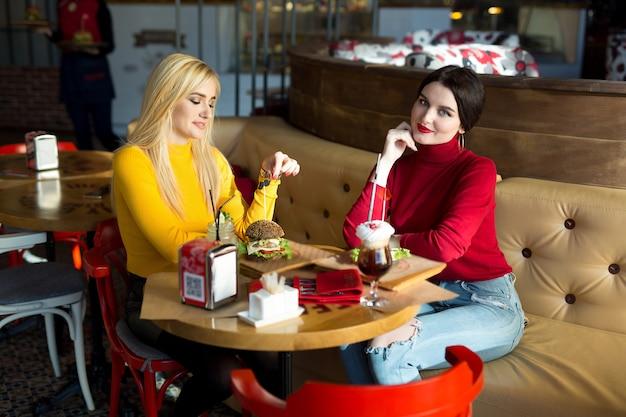 Due giovani donne in chat in un caffè