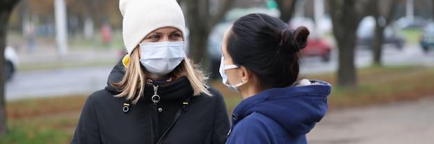 Due giovani donne che comunicano in maschere protettive all'esterno
