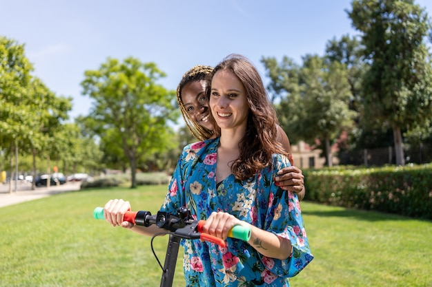 Due giovani donne di diverse etnie che usano uno scooter elettrico in giardino