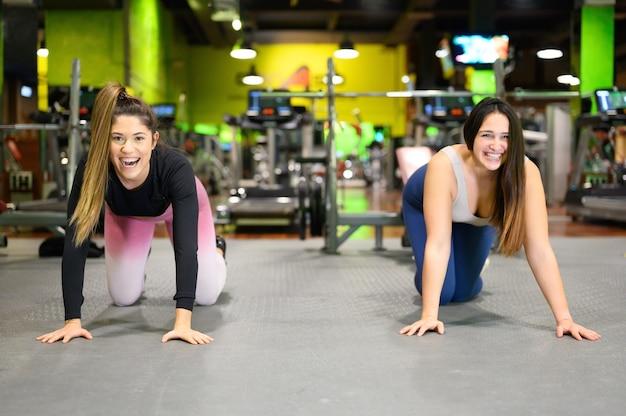 Due giovani donne che fanno tavole alte in palestra.