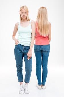 Due giovani donne vestite di t-shirt e jeans in posa. isolato sopra il muro bianco