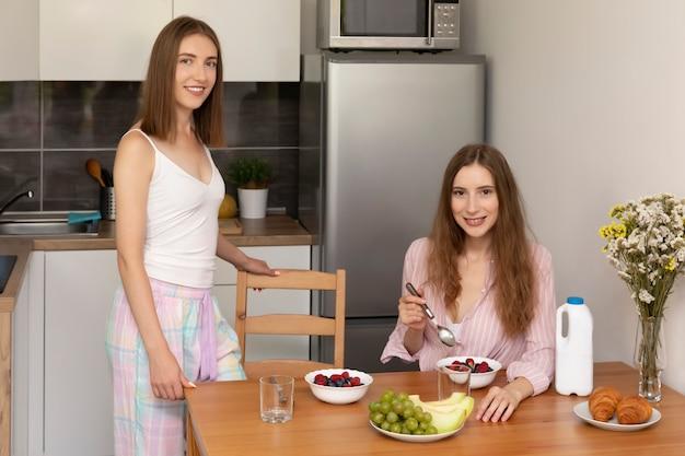 Due giovani donne fanno colazione insieme a casa in cucina