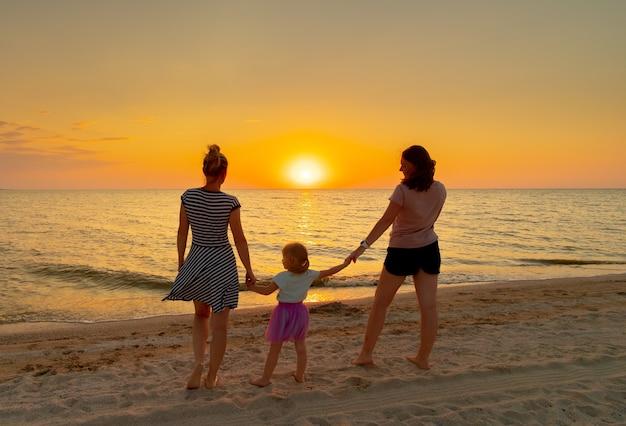 Due giovani donne tengono per mano una bambina, in piedi sulla spiaggia del mare in una sera d'estate. sullo sfondo, il sole della sera tramonta all'orizzonte.
