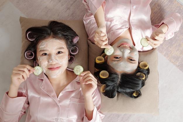 Pigiama di due giovani donne che si divertono alla festa della spa insieme a casa