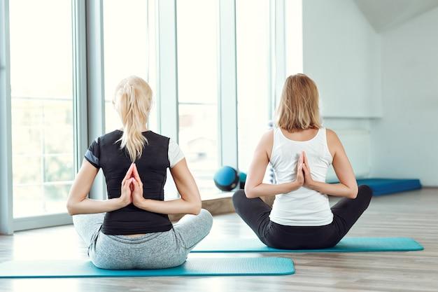 Due giovani donne che praticano yoga in palestra. ragazza che unisce le mani dietro la schiena